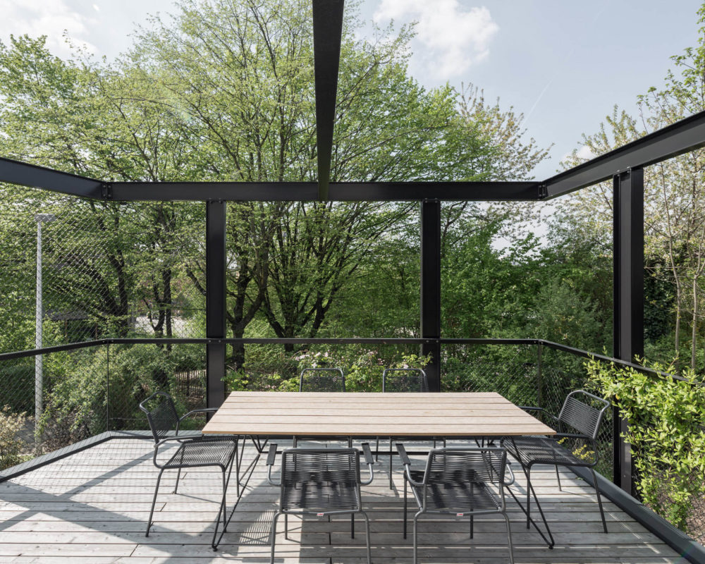 Terraza con pérgola de aluminio y mesa de madera