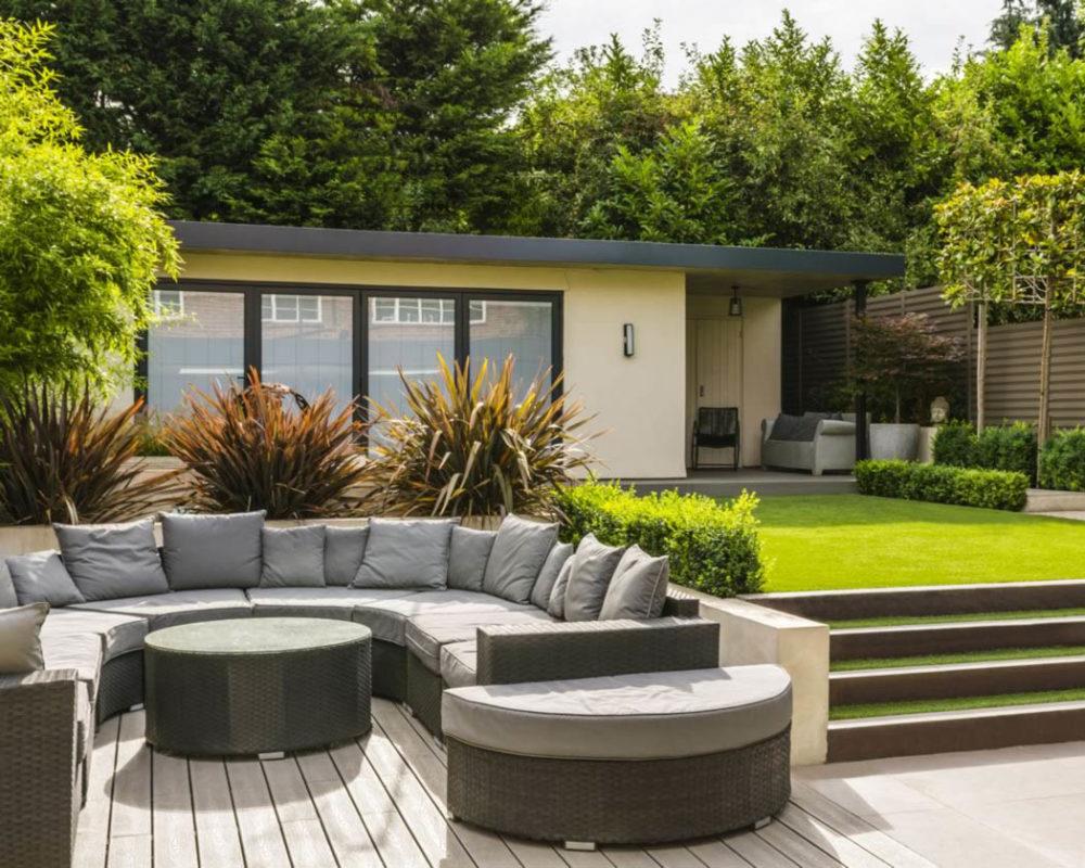 Jardin con cesped artificial junto a terraza con sofa en U
