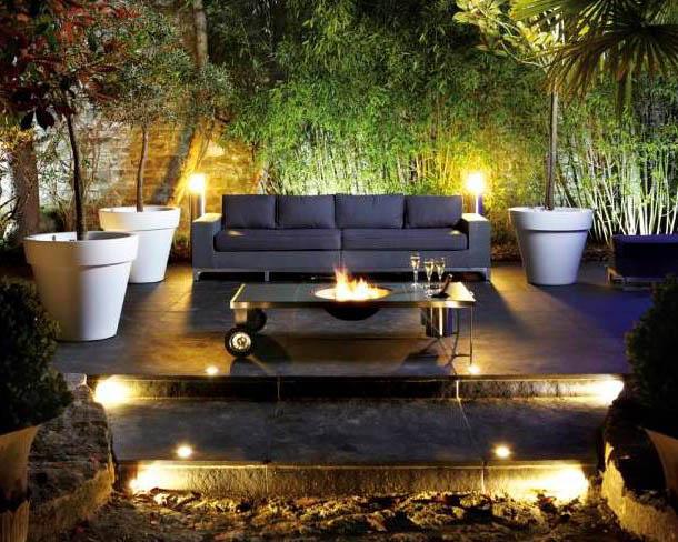 Terraza en tonos oscuros iluminada de noche con luces cálidas