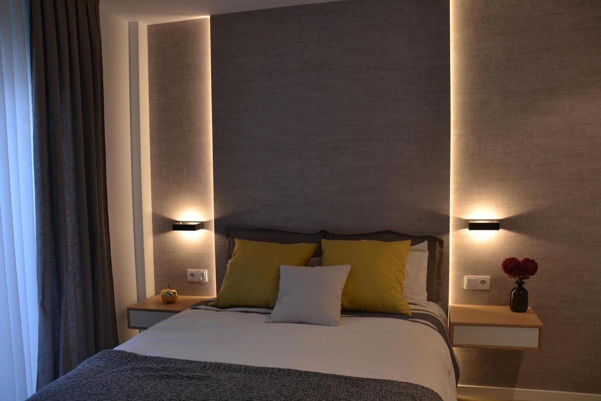 Dormitorio con cama y luces indirectas calidas