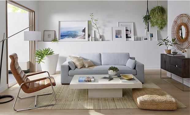 sofas en tonos claros junto a mesa blanca con alfombra de verano