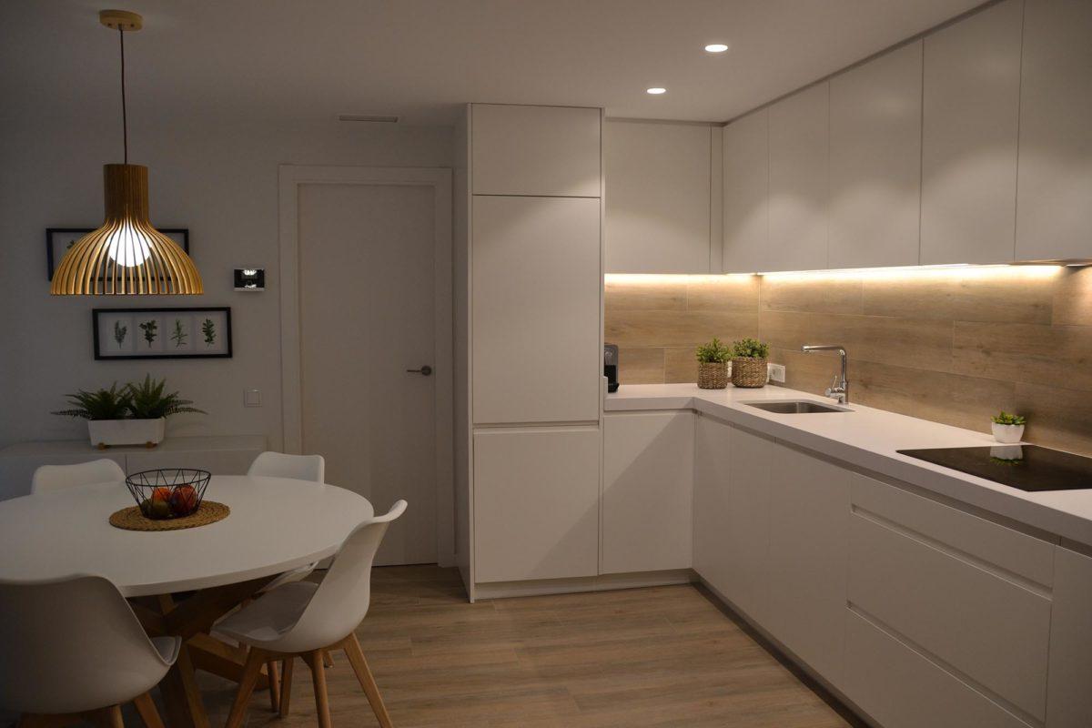 cocina de parquet con mobiliario de color blanco y mesa comedor