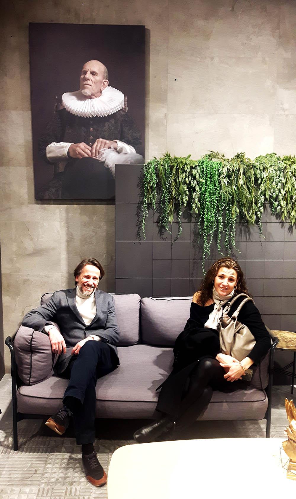 interioristas sentados en un sofa y un gran cuadro
