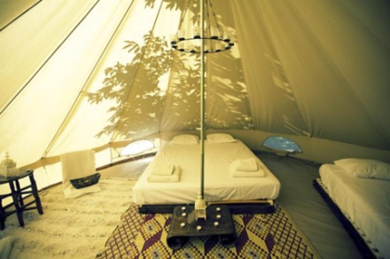 interior tienda de campaña glamping con cama y perchero