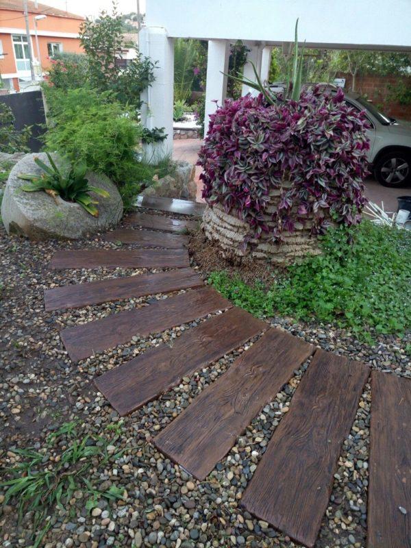 listones de madera en jardin con piedras