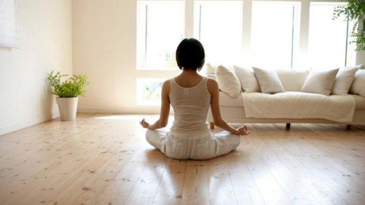 Mujer practicando yoga en casa junto a sofa y cactus