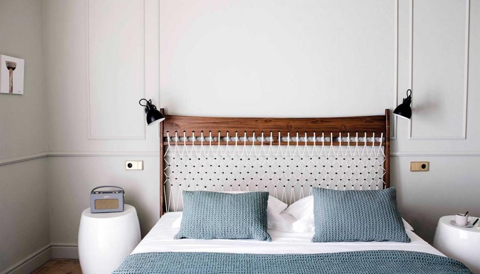 Pared blanca con molduras junto a cama matrimonio con sabanas azules
