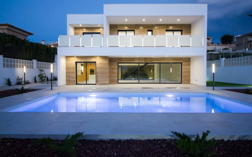 Chalet blanco con piscina iluminada