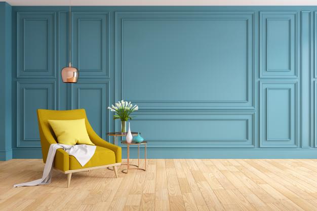 Pared azul clasico con moldura y sofa amarillo