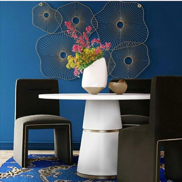 mesa blanca con sofa negro y pared azul classic blue para reformar tu casa