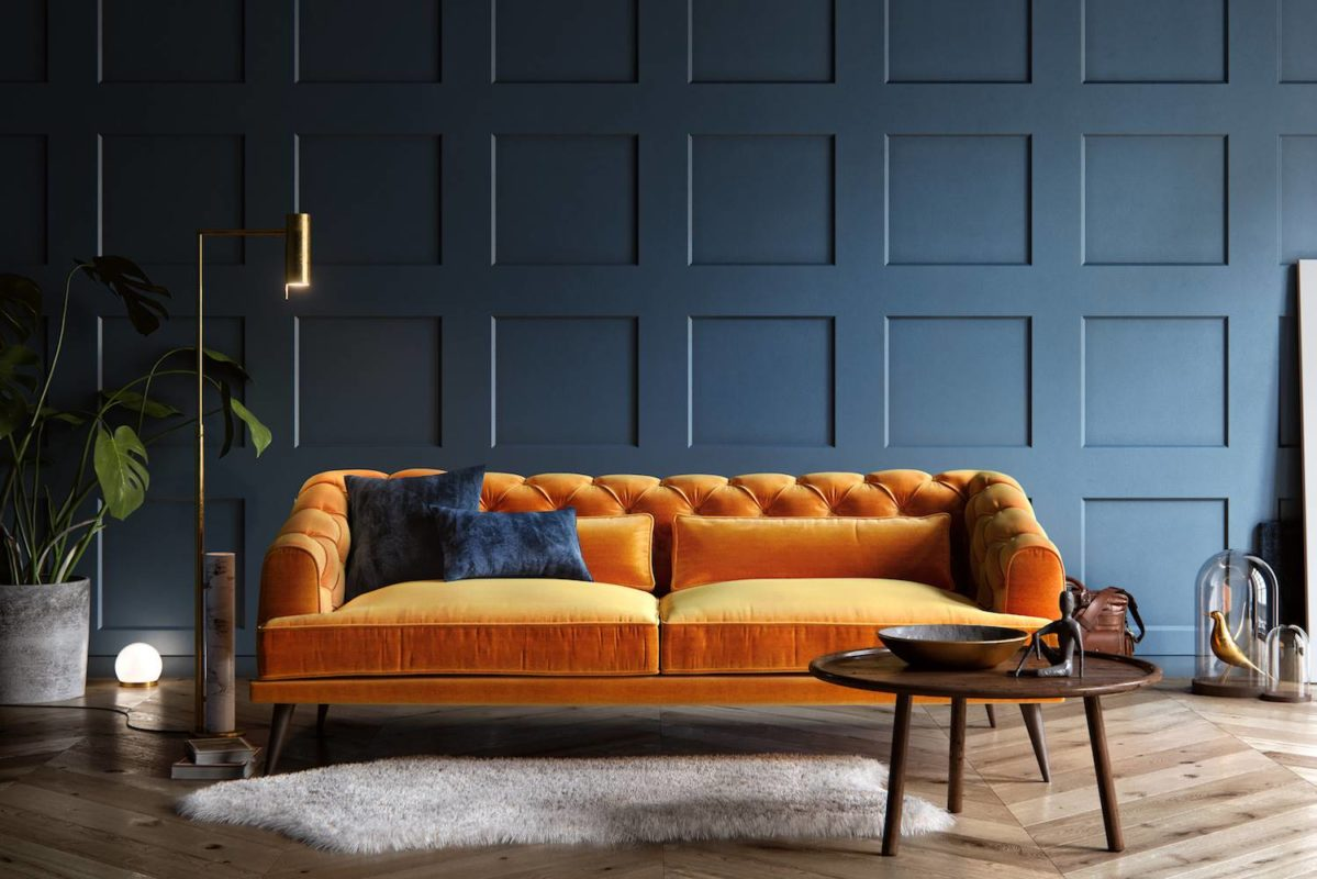 sofa naranja con alfombra y pared azul classic blue