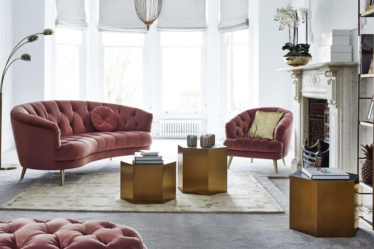 Salon estilo aos 80 con sofa rosa y mesas doradas