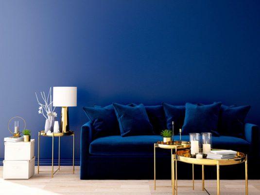 sofa azul classic blue con mesa centro dorado y pared azul
