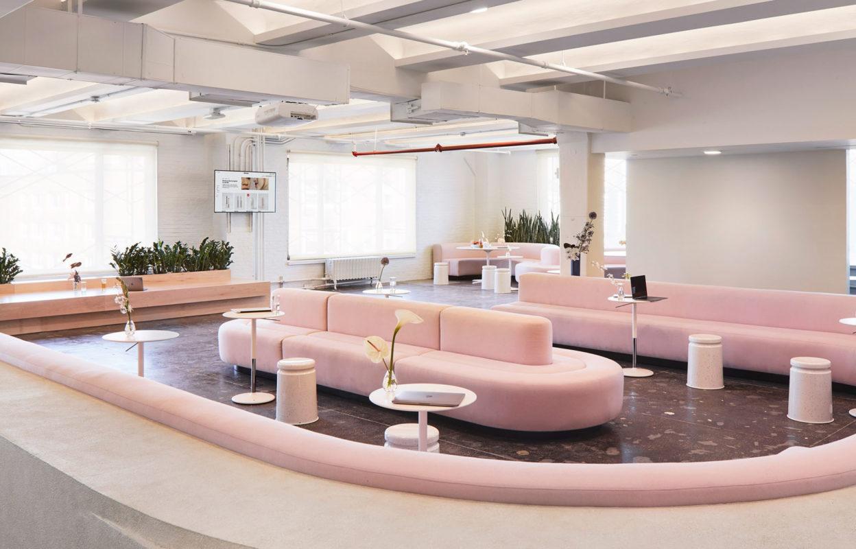 sala de estar oficina con sofas rosas