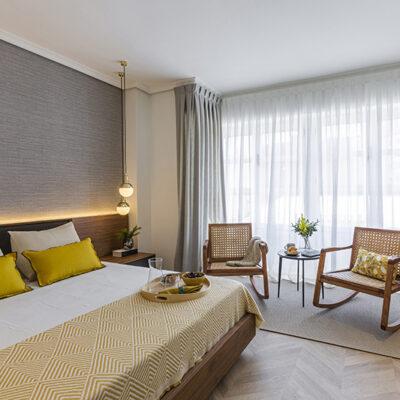 cama con dos sillas en habitacion principal