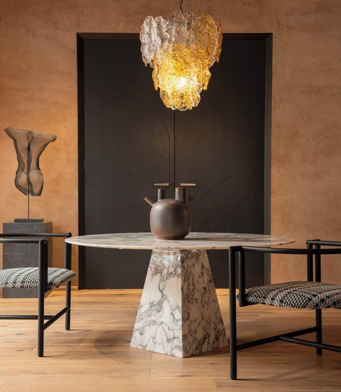 mesa diseño marmol con dos sillas oscuras