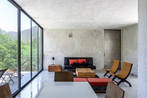salon con sofas y venanal grande al jardin