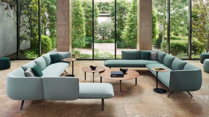 sofa verde en el salon con cristalera y jardin